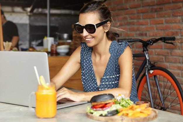 Vrouw freelancer in stijlvolle zonnebril met behulp van laptop pc voor werk op afstand
