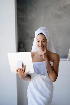 Vrouw freelancer in witte handdoekhouder in de badkamer met een laptop
