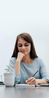 Vrouw freelancer met pen schrijven op notebook thuis of op kantoor.