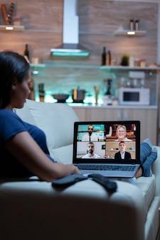 Vrouw freelancer met web chat conferentie zittend op de bank in de woonkamer. externe werknemer bespreekt tijdens online vergadering, overlegt met collega's met behulp van video-oproep en webcam die voor laptop werkt