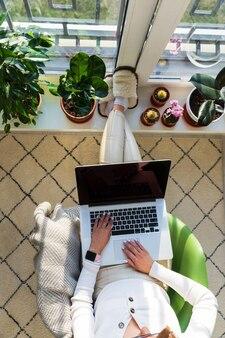 Vrouw freelancer zit op fauteuil te werken op laptop thuis en zet je voeten op de vensterbank met planten