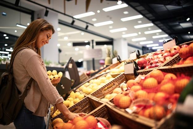Vrouw fruit kopen bij supermarkt