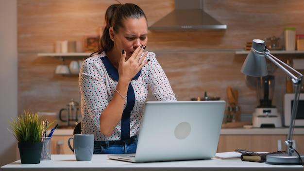 Vrouw gaapt terwijl ze 's avonds laat in de keuken op afstand vanuit huis werkt. drukke uitgeputte werknemer met behulp van moderne technologienetwerken die overuren maken voor het lezen van werk, typen, zoeken