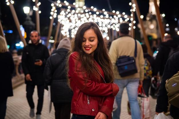 Vrouw gaat een wandeling door de stad maken met kerstverlichting