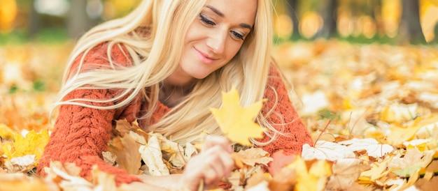 Vrouw gaat op bladeren liggen in het herfstpark