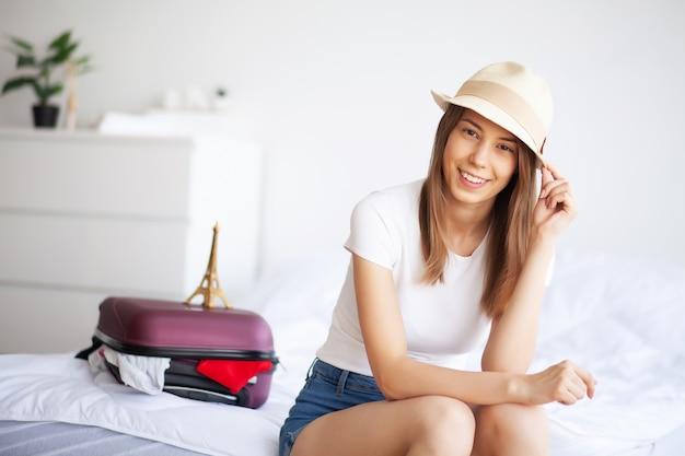 Vrouw gaat op vakantie en trekt kleding in koffer aan