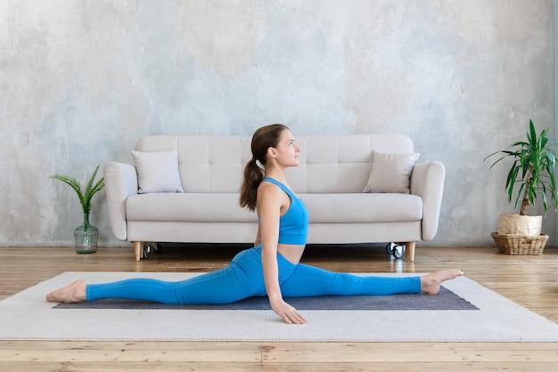 Vrouw gaat sporten doet yoga, rekken terwijl ze in een longitudinale spleet op de mat zit