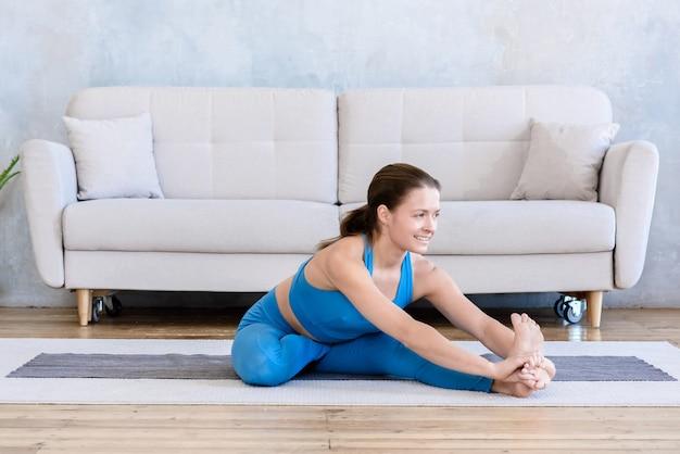 Vrouw gaat sporten thuis door yoga gymnastiek te doen om haar lichaam te strekken