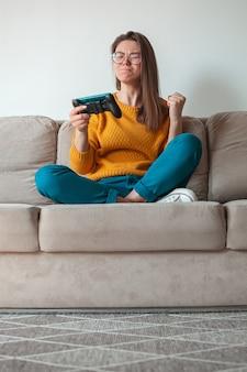 Vrouw gamer die online game voor mobiele telefoons speelt, is verliezer, in handen zittend op de bank