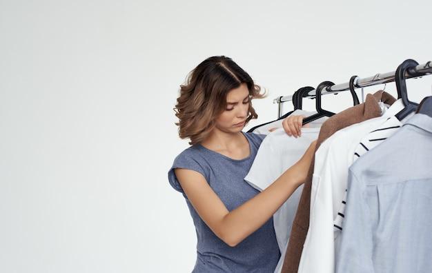 Vrouw garderobe verzorger onderzoekt kleding op een hanger winkelen shirts mode-stijl