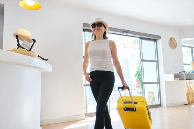 Vrouw gast toerist met koffer in hotel lobby interieur. mooie rijpe vrouw reizen, moderne hal van hotel kuuroord, vrije tijd en weekend leeftijd mensen