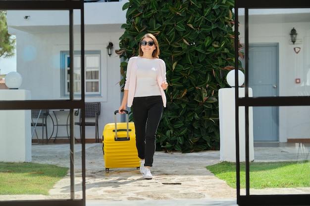 Vrouw gast toerist met koffer in hotel lobby interieur.
