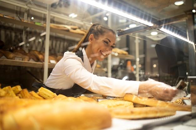 Vrouw gebak te koop in supermarkt bakkerij afdeling voorbereiden