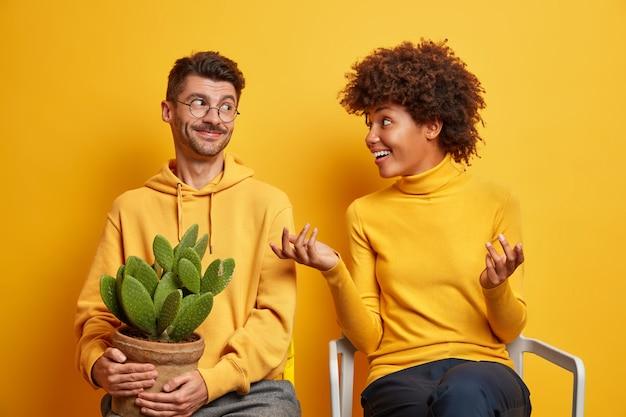 Vrouw gebaren actief en praat met man bespreken iets probeert haar idee uit te leggen verhuizen in nieuw appartement pose op stoelen op geel