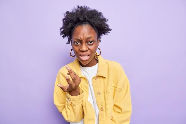 Vrouw gebaren boos kijkt verontwaardigd draagt gele jas poses op paars