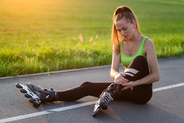 Vrouw geblesseerde knie tijdens skaten. een tiener met een blauwe plek na het vallen tijdens het inline skaten