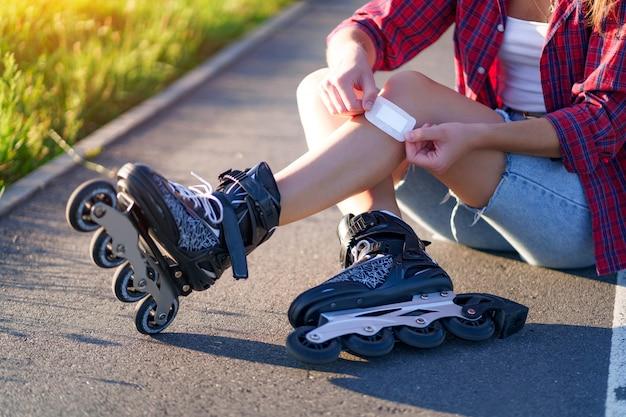 Vrouw geblesseerde knie tijdens skaten. een tiener steekt een blauwe plek met een pleister na het vallen tijdens het inline skaten