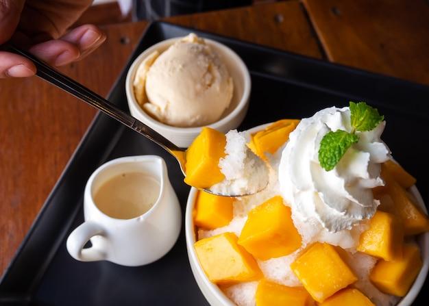 Vrouw gebruik lepel nemen geschoren ijs dessert, geserveerd met gesneden mango.