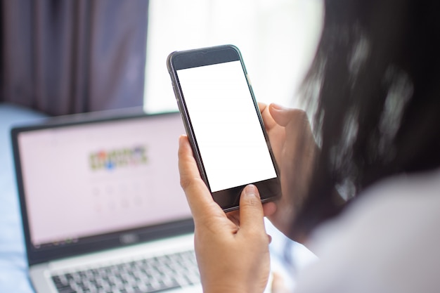 Vrouw gebruik smartphone voor internet en online winkelen met laptop. zachte focus.