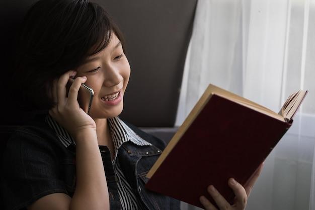 Vrouw gebruik telefoon en leesboek zitten aan de zijkant van het venster