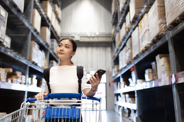 Vrouw gebruik winkelwagen voor winkelmeubilair in magazijn