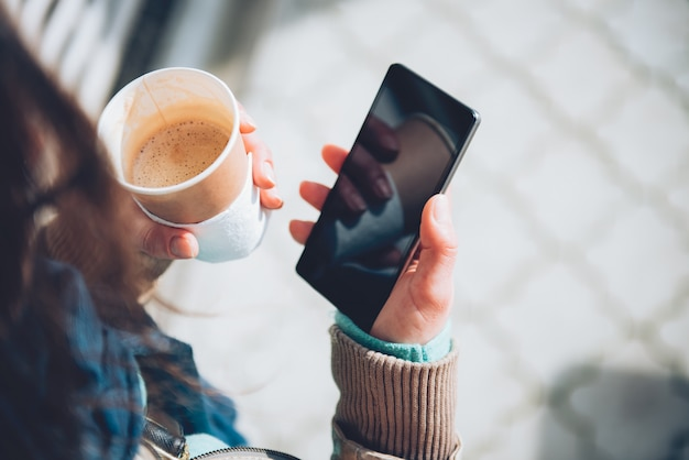 Vrouw gebruikend slimme telefoon en houdend koffie