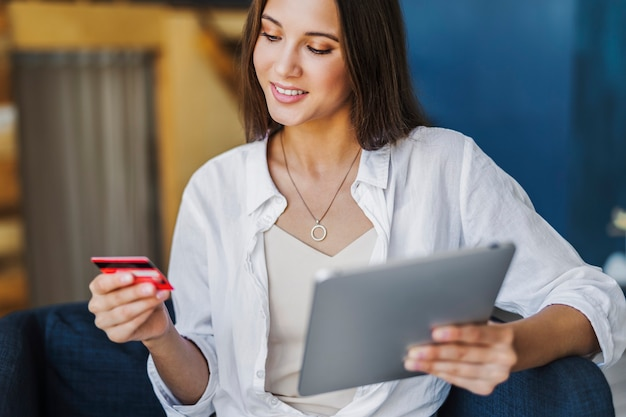 Vrouw gebruikt bankkaart om te betalen voor online gekochte goederen.