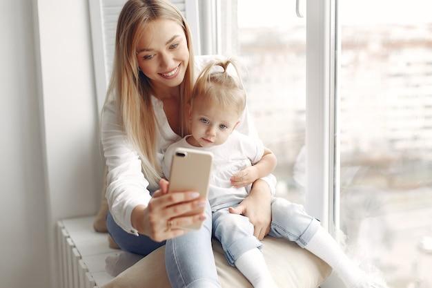 Vrouw gebruikt de telefoon. moeder in een wit overhemd speelt met haar dochter. familie heeft plezier in het weekend.