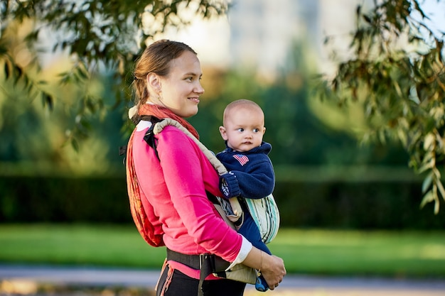 Vrouw gebruikt draagdoek om haar zoon te dragen tijdens een wandeling in het park op een zomerdag