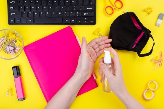 Vrouw gebruikt een antiseptische gel tijdens het werken op de computer, gele achtergrond. pandemische preventie. bovenaanzicht