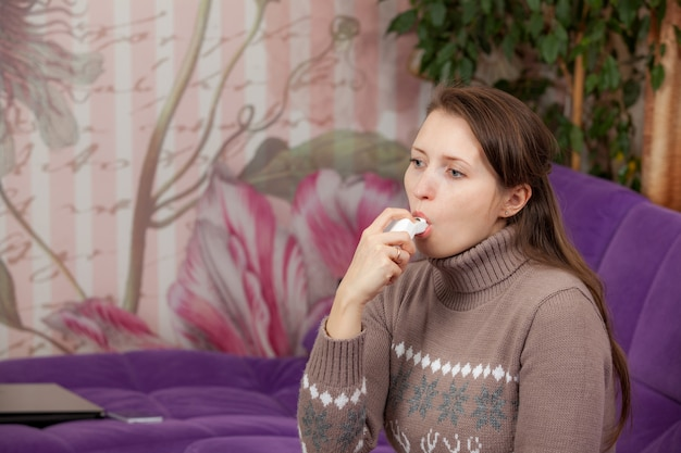 Vrouw gebruikt een inhalator tijdens een astma-aanval