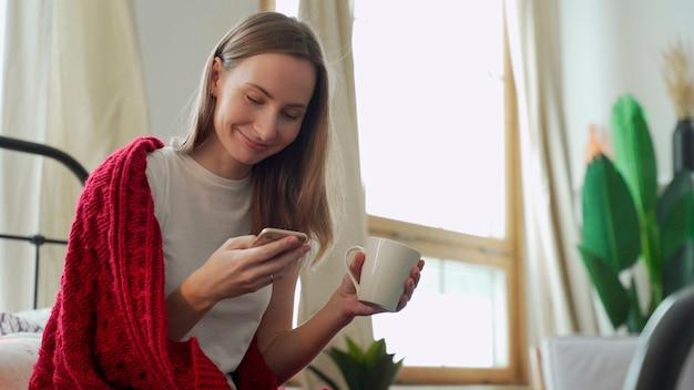 Vrouw gebruikt een mobiele telefoon voor online chat, online communicatie, ontvangt een sms-bericht, zit op het bed bedekt met een deken en houdt een mok vast