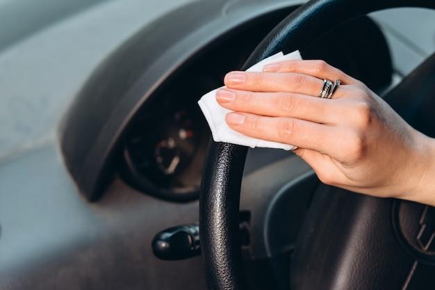 Vrouw gebruikt een ontsmettingsmiddel tijdens het autorijden. voorzorgsmaatregelen tijdens de coronavirusepidemie. zekering van covid-19. meisje in een medisch masker in een auto.