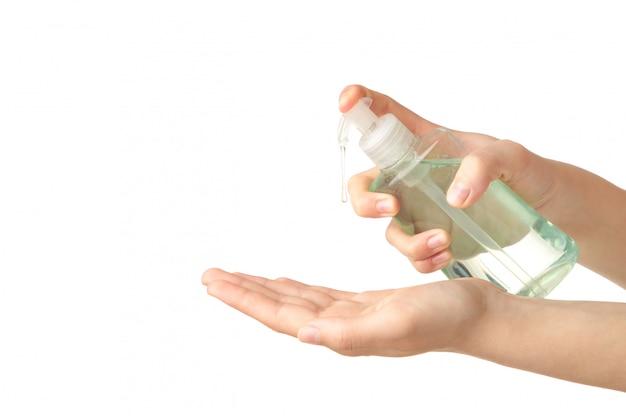 Vrouw gebruikt een ontsmettingsmiddel voor haar handen om handen te reinigen om corona-virus covid-19 te voorkomen. op wit wordt geïsoleerd