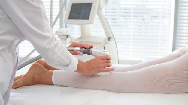 Vrouw gebruikt een professioneel apparaat tijdens een vacuümmassageprocedure