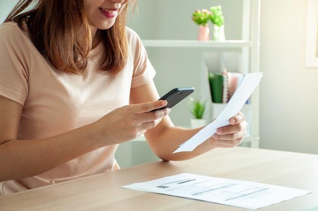 Vrouw gebruikt een smartphone om de streepjescode te scannen om maandelijkse telefoonrekeningen te betalen na ontvangst van een naar huis verzonden factuur