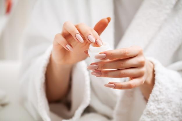 Vrouw gebruikt een vochtinbrengende crème om haar huid te verzorgen