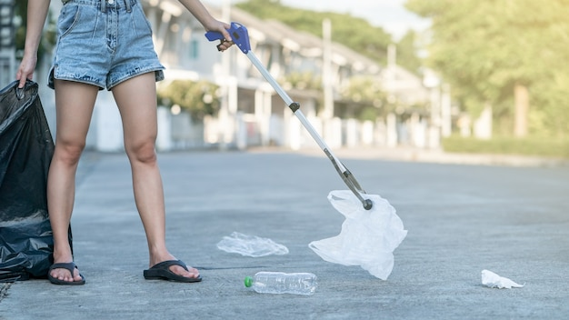 Vrouw gebruikt garbage collector apparatuur om plastic afval in een zwarte zak op de grond te houden.
