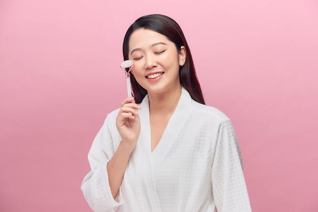 Vrouw gebruikt jade roller voor gezichtsmassage