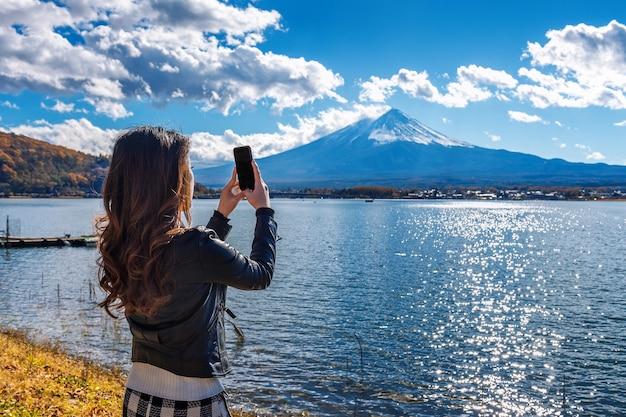 Vrouw gebruikt mobiele telefoon om een foto te maken bij fuji-bergen, kawaguchiko-meer in japan.