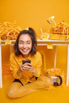 Vrouw gebruikt mobiele telefoon om online met vrienden te chatten tijdens werkpauze gekleed in stijlvolle kleding heeft vrolijke uitdrukkingshoudingen in kast in de buurt van werkplek heeft deadline om taak af te maken