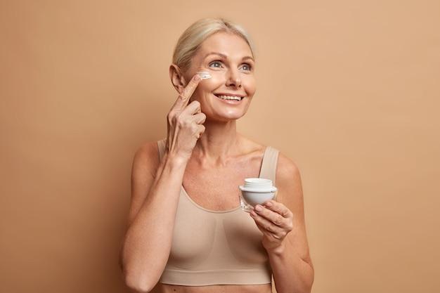 Vrouw gebruikt schoonheidsproduct brengt voedende gezichtscrème aan om de huid te hydrateren, geconcentreerd met een dromerige uitdrukking