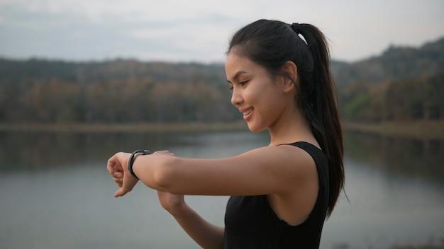 Vrouw gebruikt smartwatch tijdens het sporten in de natuur buiten bij zonsondergang