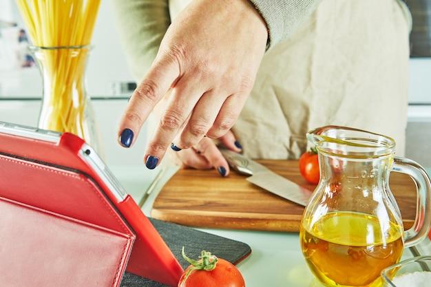 Vrouw gebruikt vingerdia op tabletscherm koken volgens de tutorial van online virtuele masterclass,