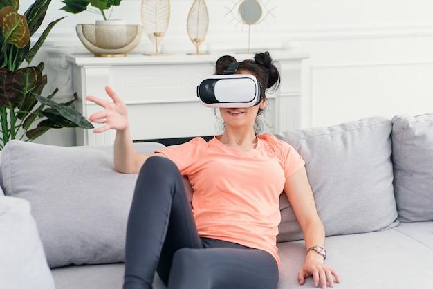 Vrouw gebruikt vr-bril thuis op de bank. technologieën van de toekomst.