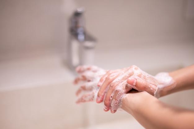 Vrouw gebruikt zeep handen wassen onder de waterkraan.