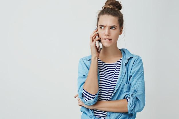 Vrouw geconfronteerd met moeilijke moeilijke keuze perplex bijten onderlip fronsend serieus opzij kijkend smartphone houden praten hard praten, denken, nemen van beslissing