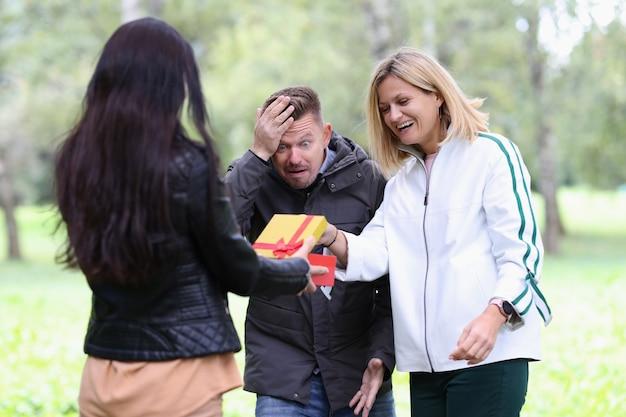 Vrouw geeft cadeau aan vriend met vriendje in parkverrassingen voor vriendenconcept