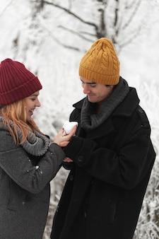 Vrouw geeft hart vorm gemaakt van sneeuw aan haar vriendje
