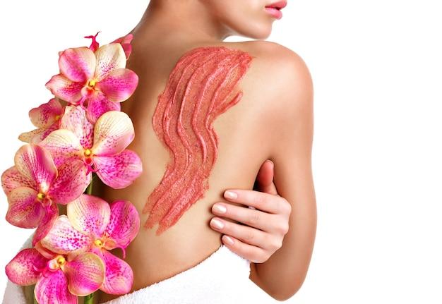 Vrouw geeft om de huid van het lichaam met behulp van cosmetische scrub op de rug - geïsoleerd op wit